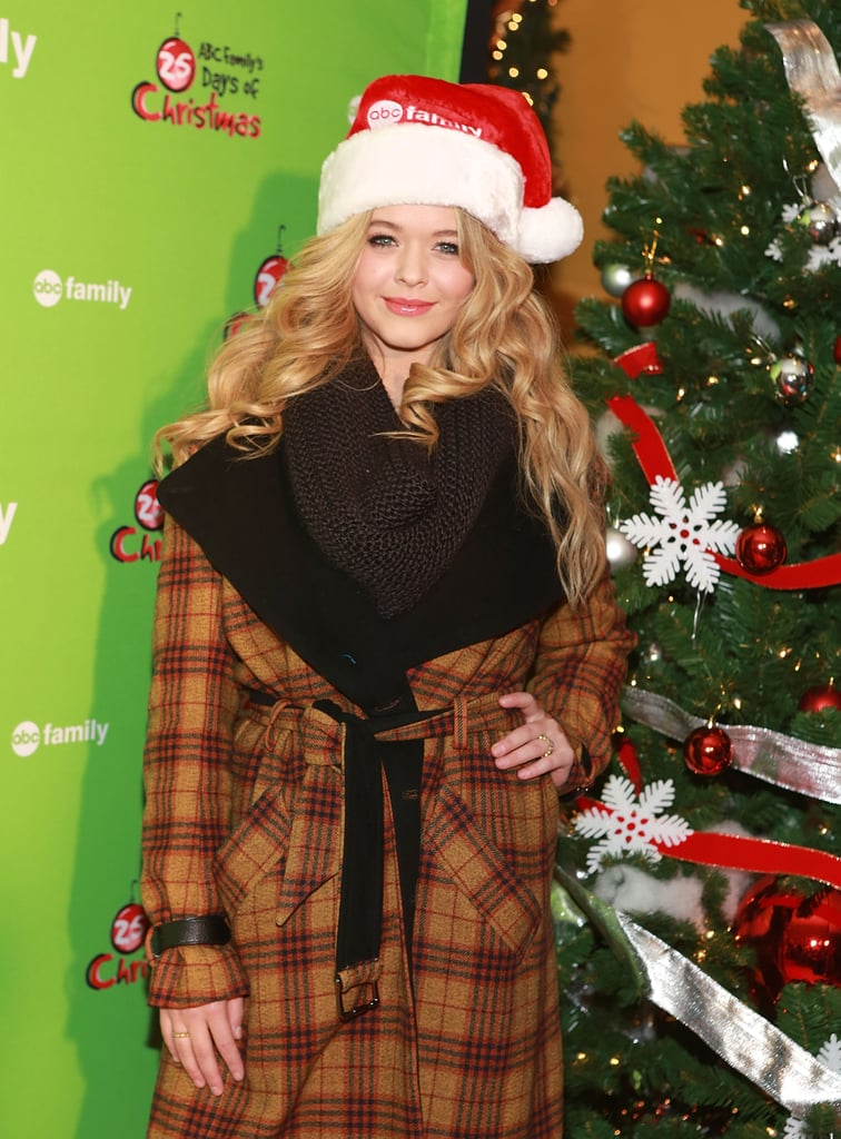 Pretty Little Liars star Sasha Pieterse rocked a red hat instead of a red coat at Rockefeller Center in NYC.