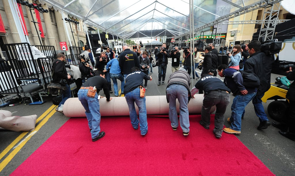 It takes five guys to roll out the giant red carpet.