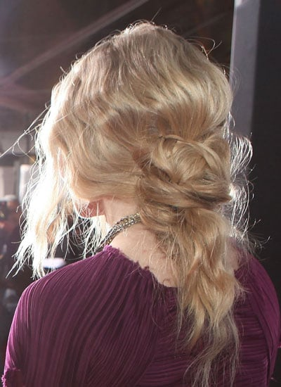 Place the bottom section, incorporating pieces from the very front, into a very loose ponytail at the base of the neck. Then place the top section into a loose ponytail right above the bottom ponytail, positioning the top ponytail slightly askew. Be sure to leave out a few face-framing pieces.