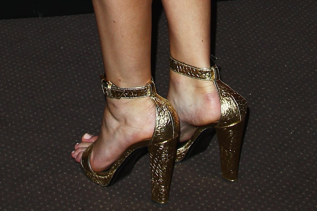 Jennifer paired her black dress with metallic gold Tom Ford ankle strap sandals.