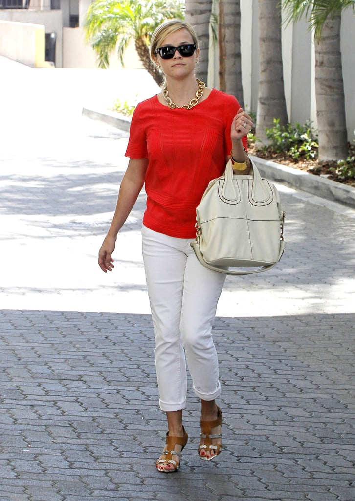 Just another Summer hit from Ms. Witherspoon: a vibrant top, white denim, and Pedro García sandals — not to forget her luxe Givenchy tote.