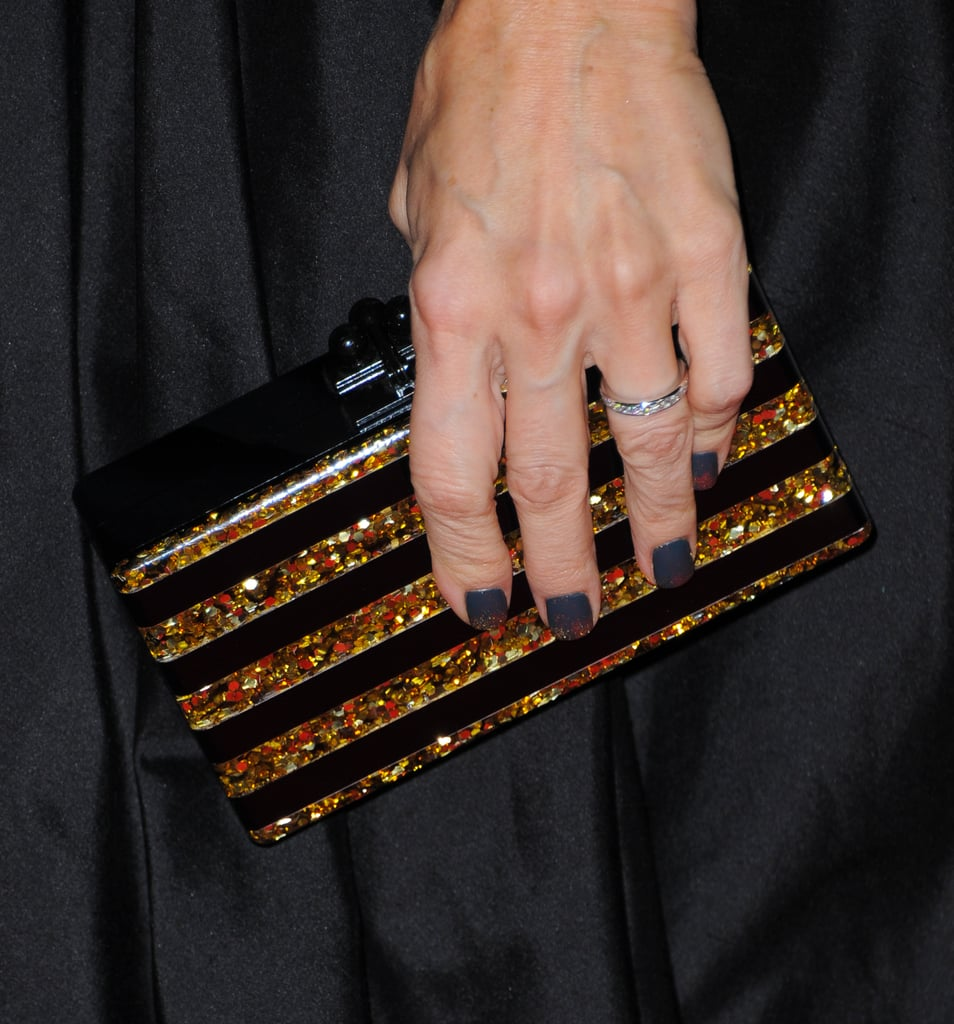 Monica Potter's striped Edie Parker clutch struck just the right note against her black and gold gown.