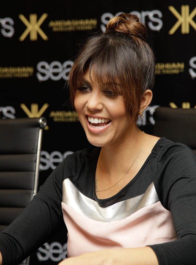Kourtney Kardashian paired her rounded fringe with a loose topknot for a fashionable effect.