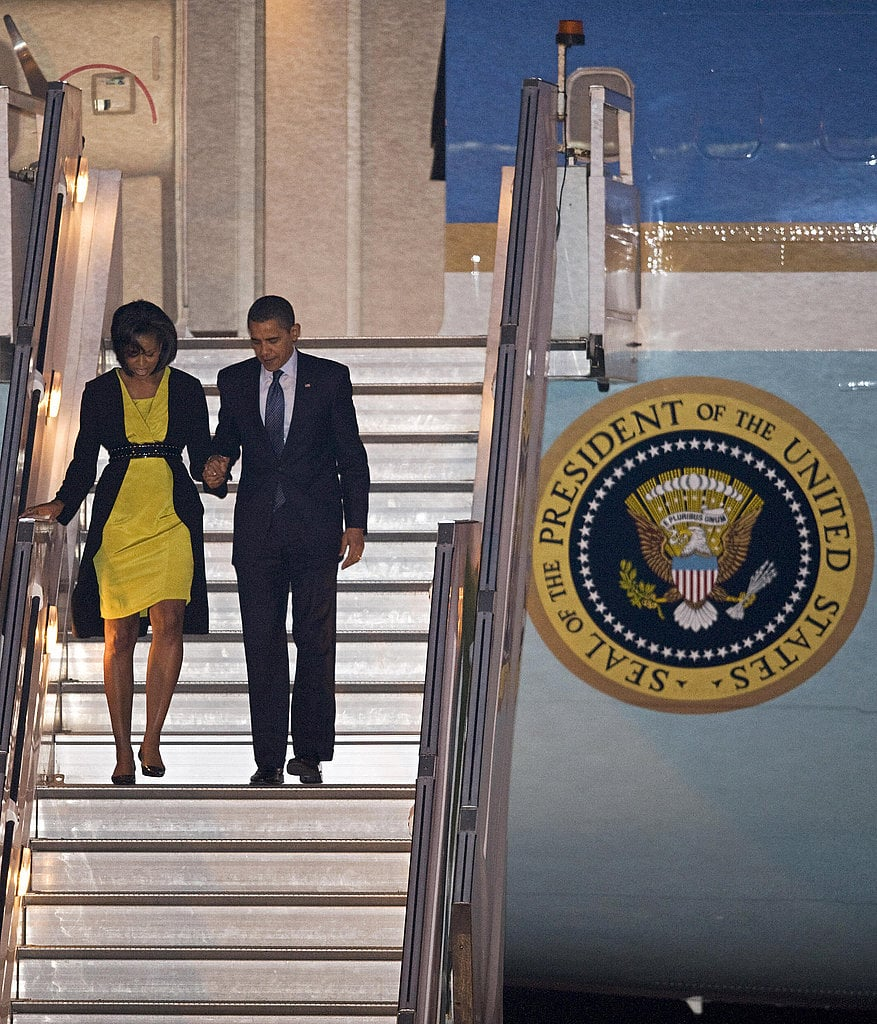 Michelle wowed upon deplaning from Air Force One in a bright yellow Jason Wu dress with a black Michael Kors coat, cinched with a black Alaia belt.