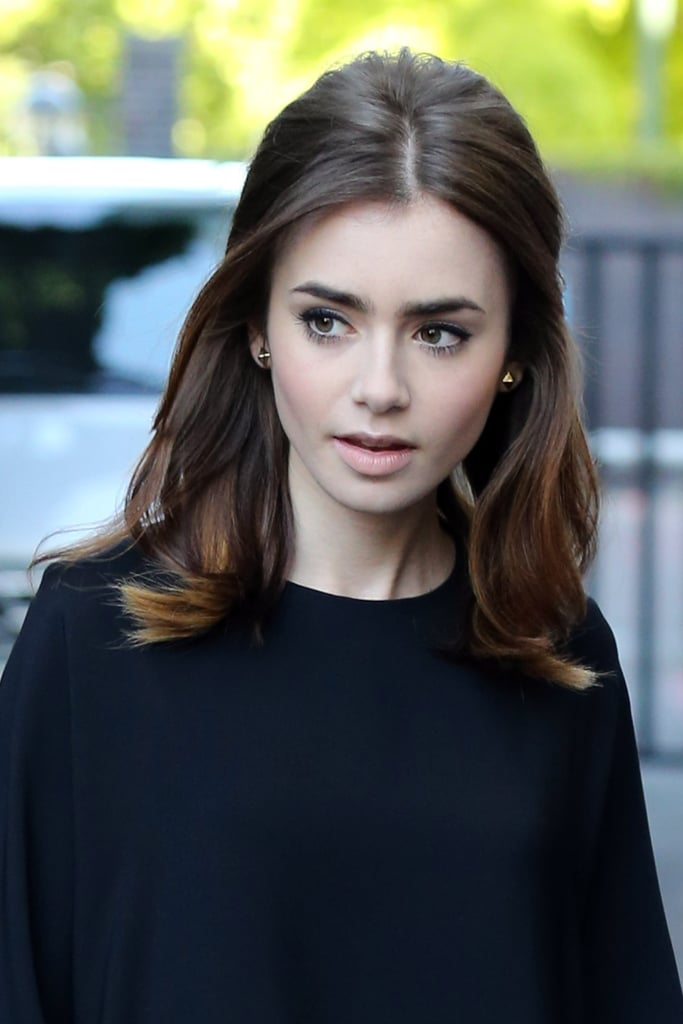 Lily Collins had a slight '60s vibe to her beauty look while in the UK. Light pink lipstick, a voluminous blow dry, and a flick of eyeliner were the key elements of her look.