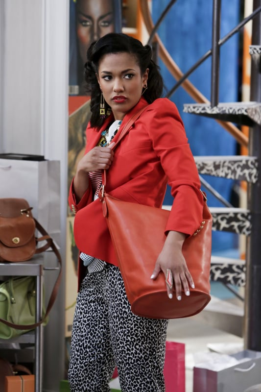 Larissa accessorised her fitted red blazer with an orange leather Coach duffel. Source: The CW