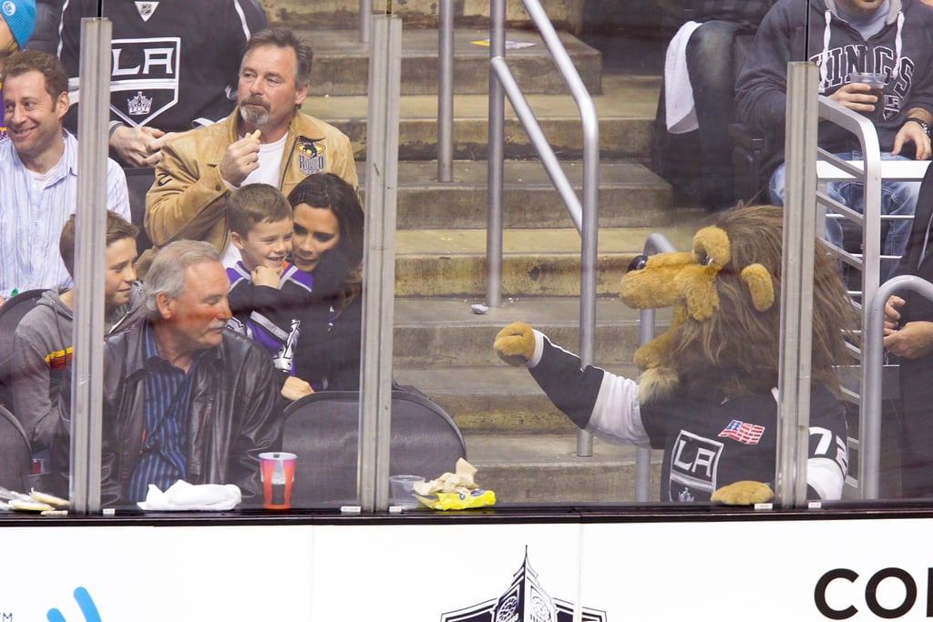 Victoria Beckham held onto son Cruz Beckham and Brooklyn Beckham as they were greeted by the mascot at a hockey game in LA.