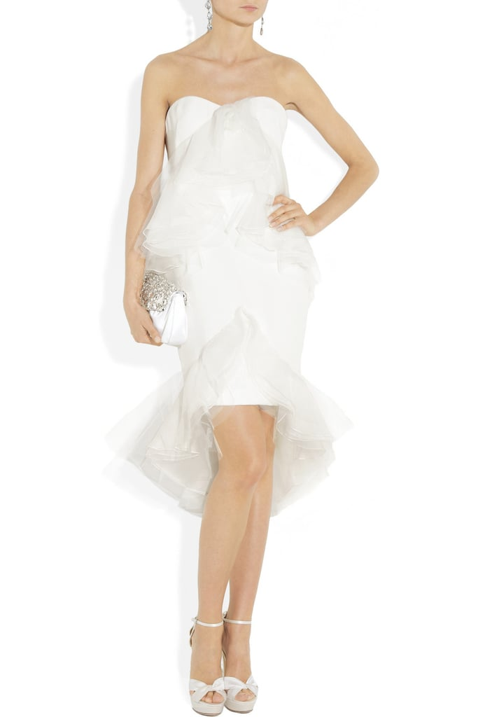 """This Marchesa dress is the epitome of a modern fairy tale. I love the length — it allows you to show off an amazing pair of heels! — and the mix of structured and floaty, which gives off an elegant, avant-garde vibe. It's perfect for the bride who wants to look amazing but doesn't take herself too seriously."" — Brittney Stephens, assistant editor Marchesa Ruffled Silk-Crepe Strapless Dress ($3,500)"