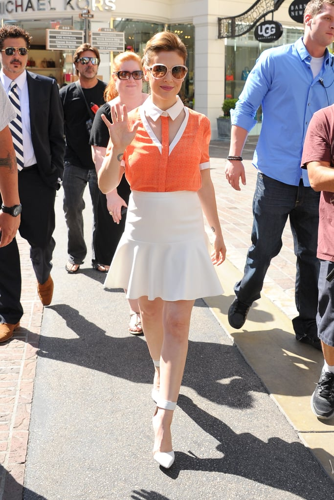 Alyssa Milano delivered ladylike with a side of sass in an orange collared cutout blouse, a flared white skirt, and white ankle-strap pumps while strutting through The Grove mall in LA.