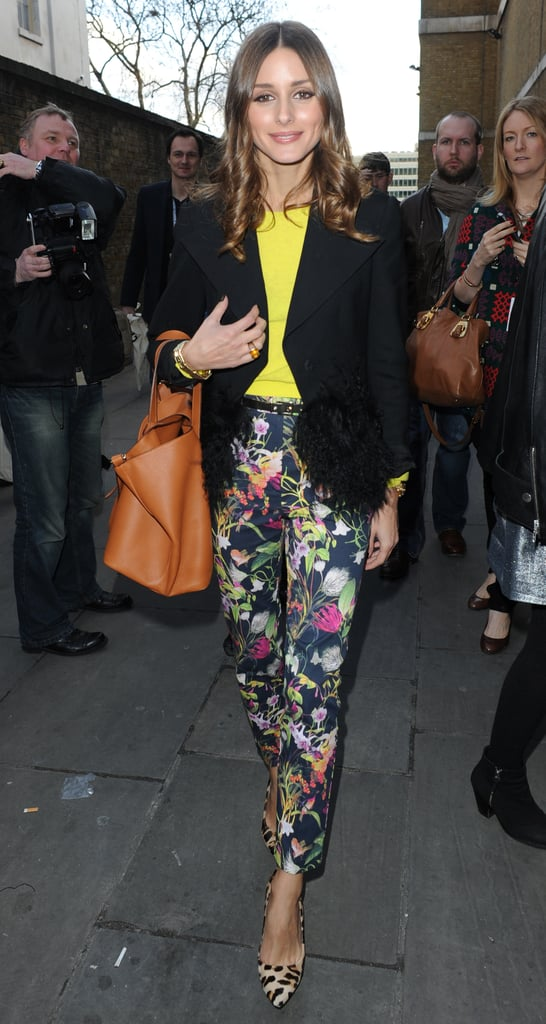 Olivia Palermo paired her Topshop floral pants with a neon sweater and black blazer at London Fashion Week.   More Tory Burch...