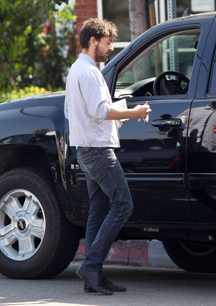 Shia LaBeouf walked to his car with a cup in his hand.