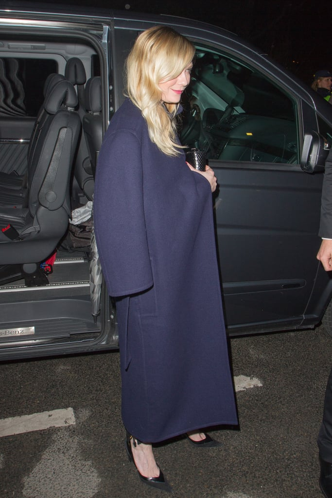 Kirsten Dunst covered up in a long navy coat and black pointy pumps during her Saint Laurent arrival at PFW.