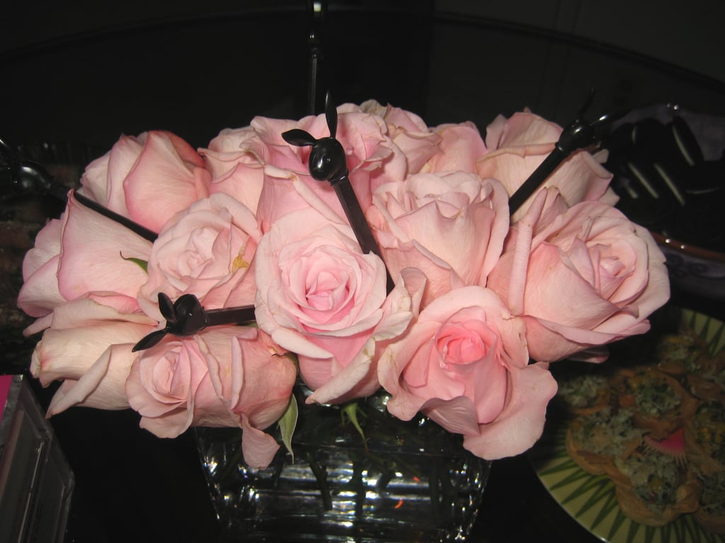 The floral arrangements were pale pink roses in clear glass vases. Black Playboy Bunny drink stirrers added a kitchy-cool touch to one of the arrangements.