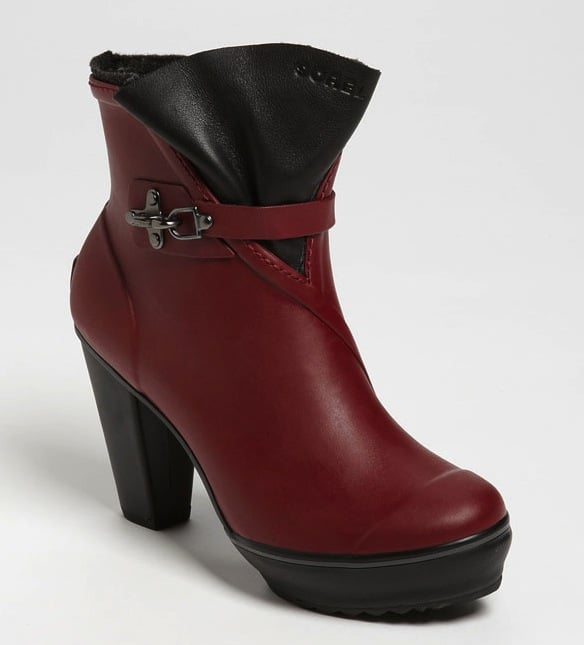 """This is one of those """"you can have your cake and eat it too"""" moments. Introducing the Sorel Medina Rain Boot ($200): it's puddle-proof and has all the appeal of a chic-meets-slightly undone ankle boot in a sensuous shade of red."""