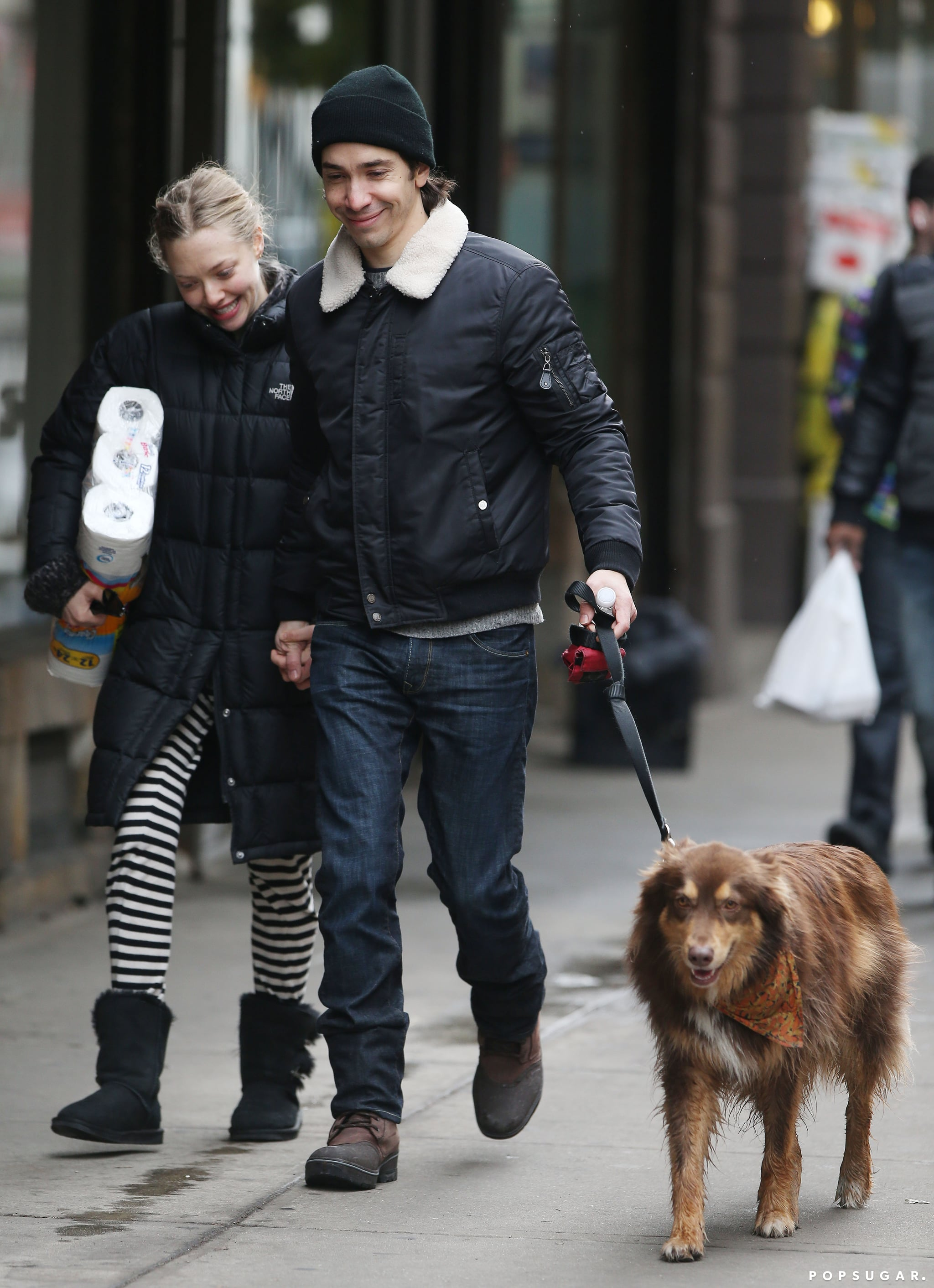 They hold hands while walking her dog.