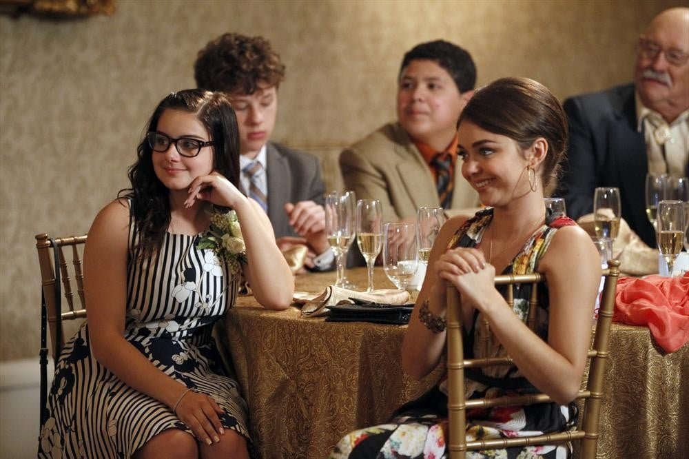 Alex (Ariel Winter) and Hayley (Sarah Hyland) sit at the kids' table.