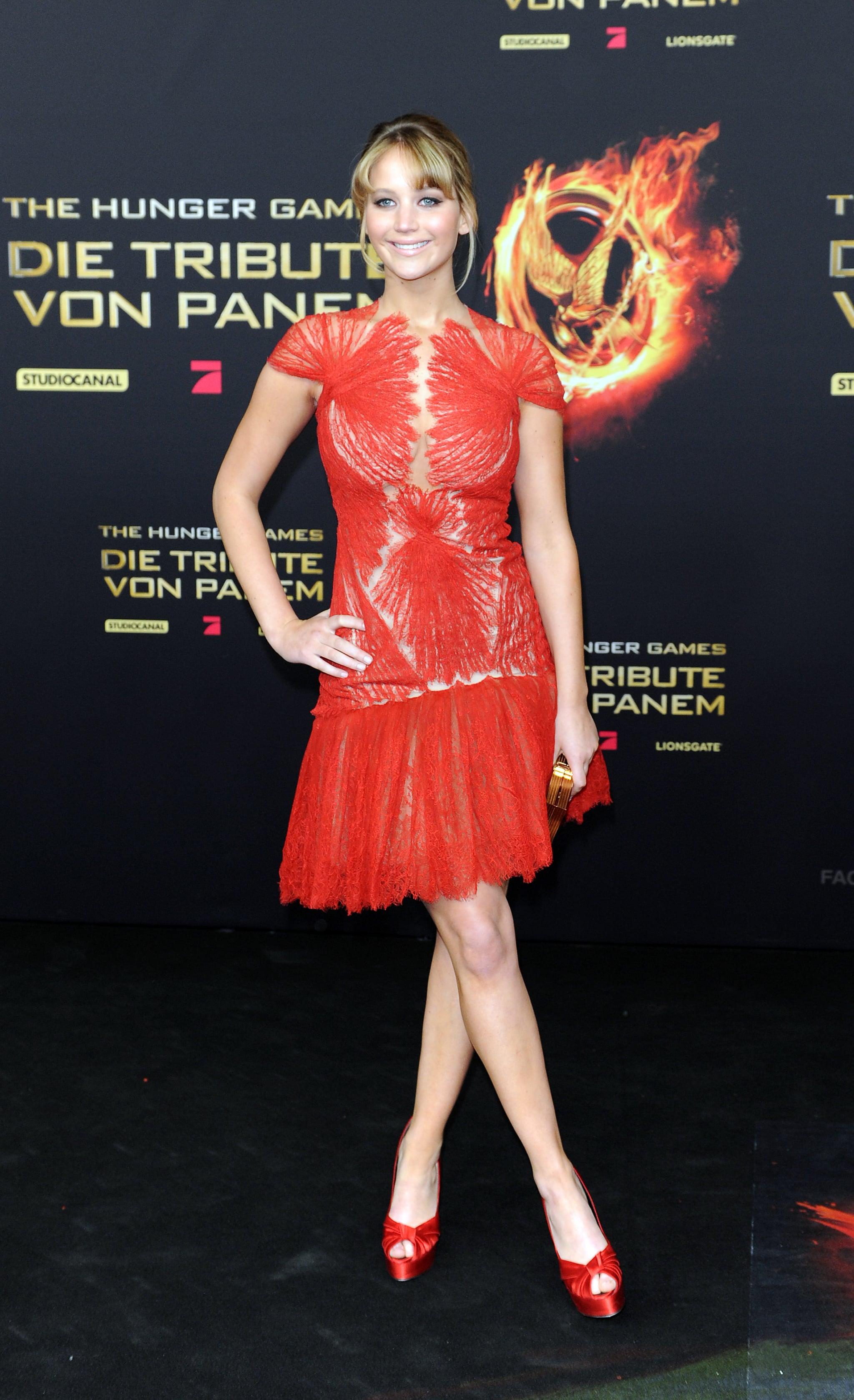 Jennifer Lawrence stepped out for the Berlin premiere of The Hunger Games in a this flirty, feminine Marchesa, red Giuseppe Zanotti heels to match, and a gold Ferragamo clutch in hand –  the perfect balance of femininity and sex appeal.