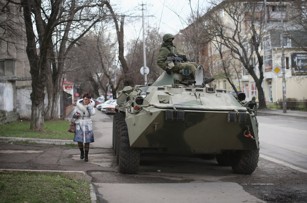 Signs of a possible conflict between pro-Russian and Ukrainian forces came after Putin signed a treaty to annex Crimea. On Tuesday, Russian military personnel surrounded a Ukrainian military base in Simferopol, and when masked gunmen descended on the base, a member of the Ukrainian military was killed. The next day, nearly 300 armed pro-Russian supporters took over a Ukrainian navy headquarters in Sevastopol, replacing Ukrainian flags with Russian flags.