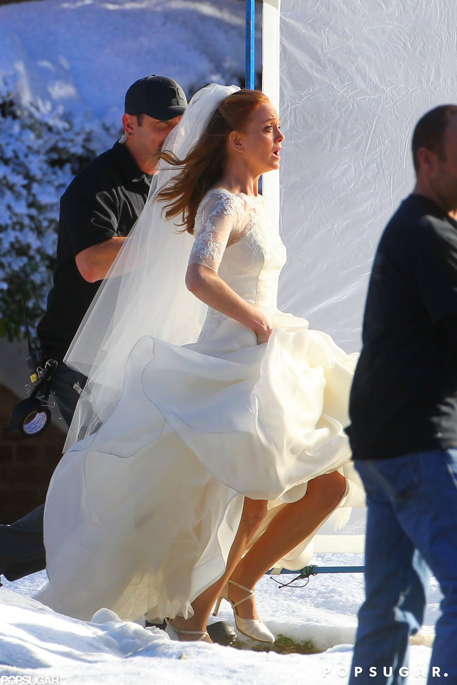 Jayma ran out of a building in a wedding dress.