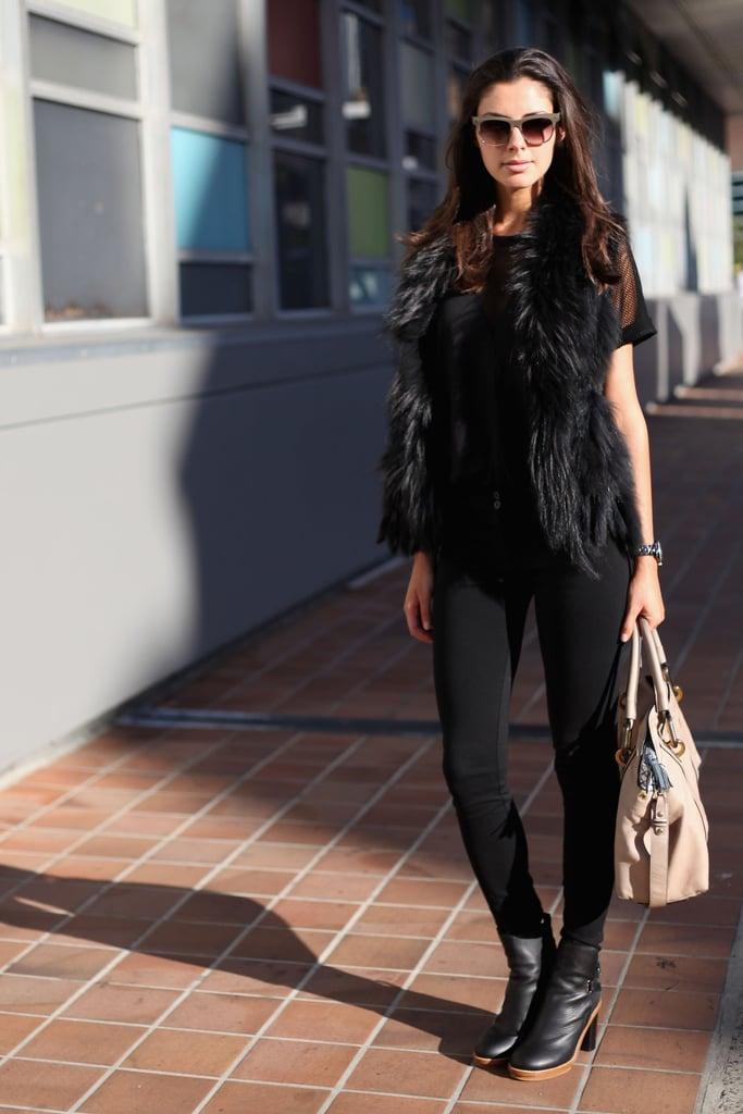 Taking a darker stance on warm-weather dressing, this stylish lady wore head-to-toe black and accented the look with a neutral-toned tote and retro sunglasses.