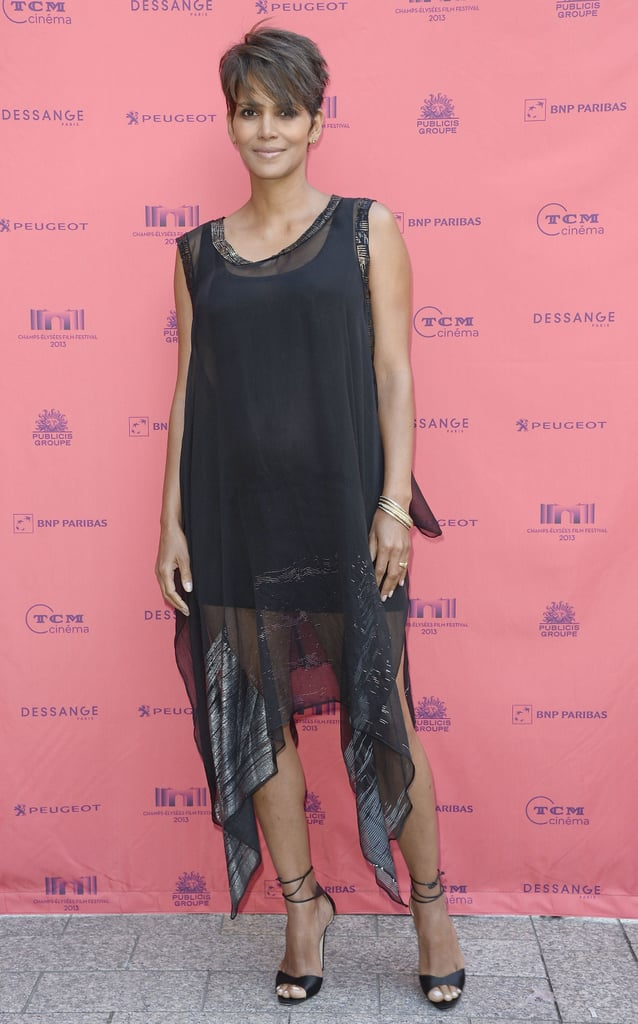 At the 2013 Champs-Élysées Film Festival in Paris, Halle Berry was insanely fashionable in a little black sheer dress and ankle-strap sandals. We love the asymmetrical hemline and subtle embellishments.
