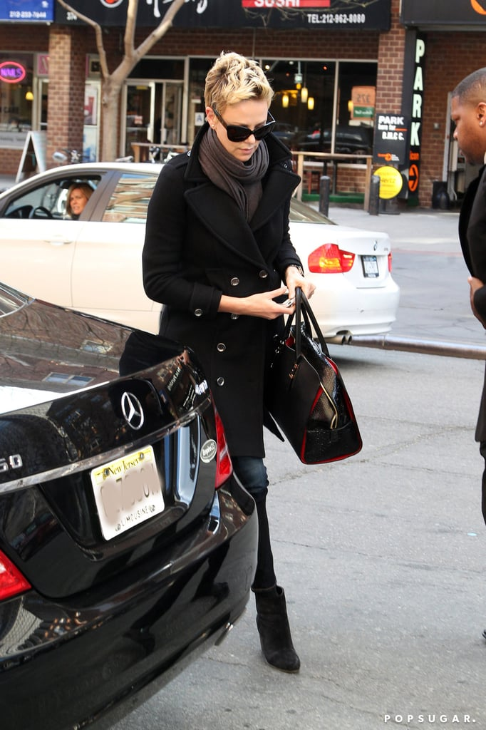 Charlize Theron wore a black peacoat and sunglasses.