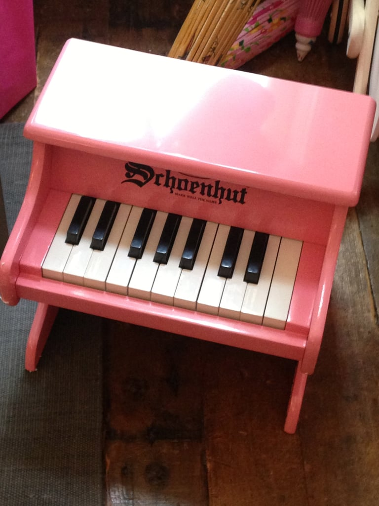 We can't decide what the cutest thing about this petite piano is — the bubblegum pink paint job, or its tiny size.
