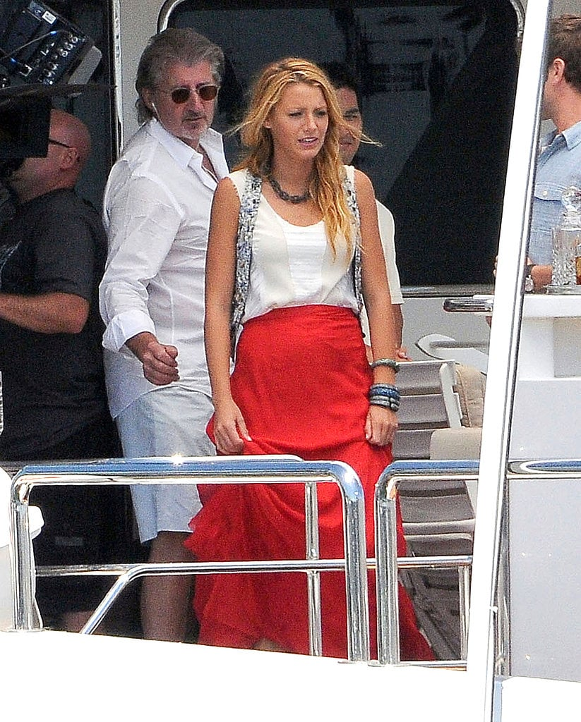 Blake Lively sported a shimmery silver vest by Matthew Williamson, a white tank and red maxi skirt by Rag & Bone, and bold metallic jewels while shooting a scene on a boat.