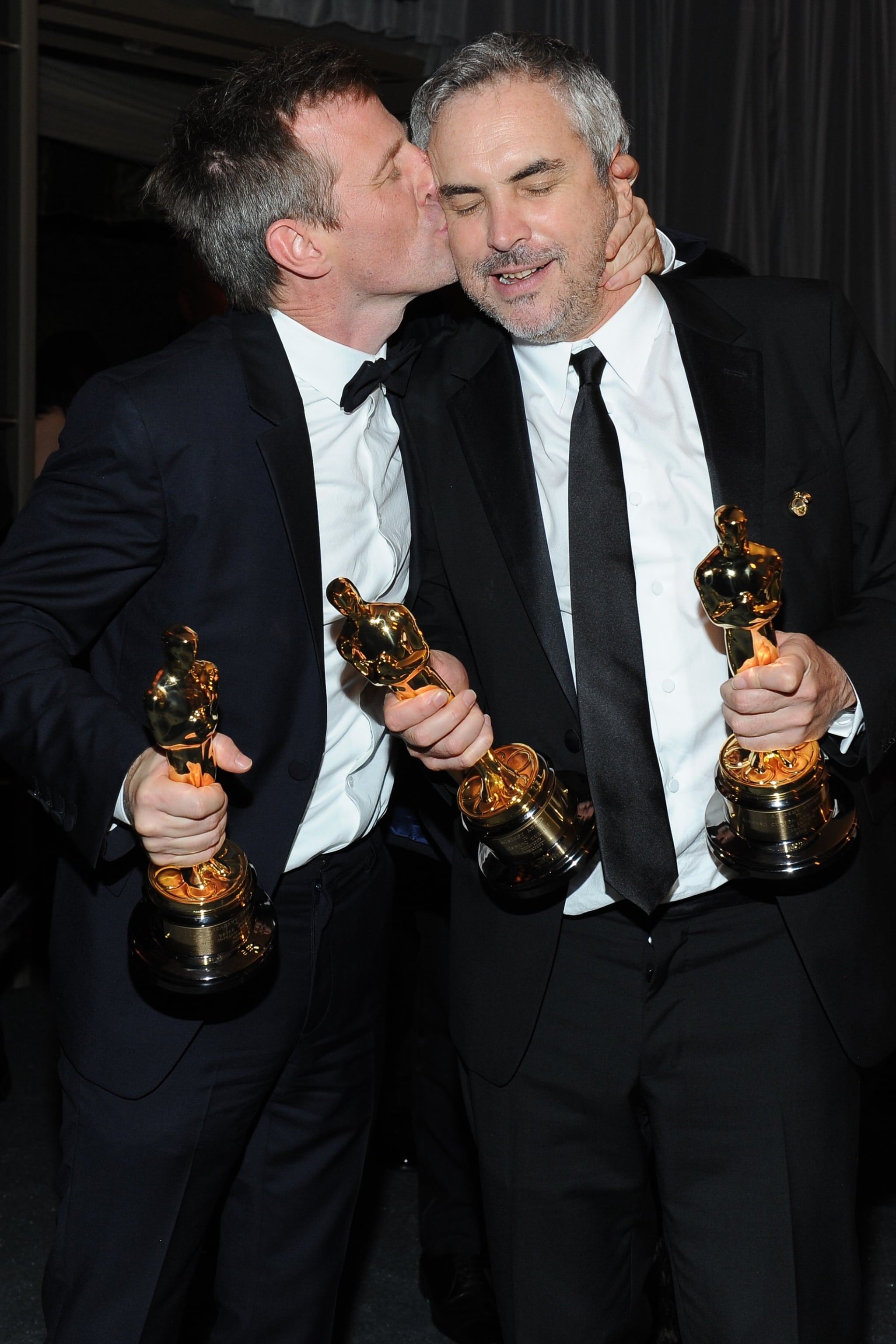 Spike Jonze, who won the Oscar for best original screenplay for Her, planted one on best director winner for Gravity Alfonso Cuarón.