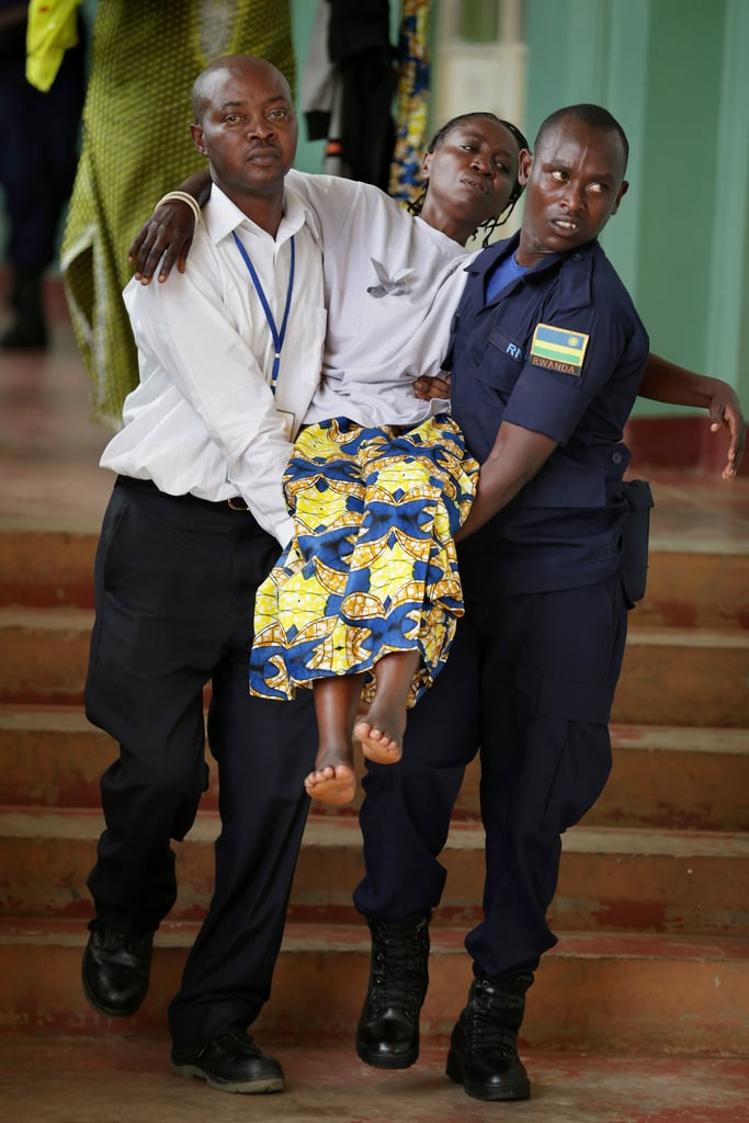 Security officials carried a distraught Rwandan away from the crowds.