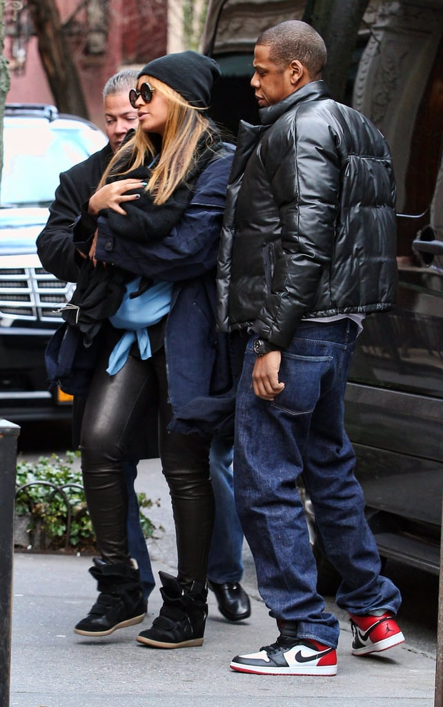 Beyoncé carried baby Blue Ivy in slick leather pants and a black beanie while Jay Z followed behind in a stylish puffer jacket and Nikes in February 2012.