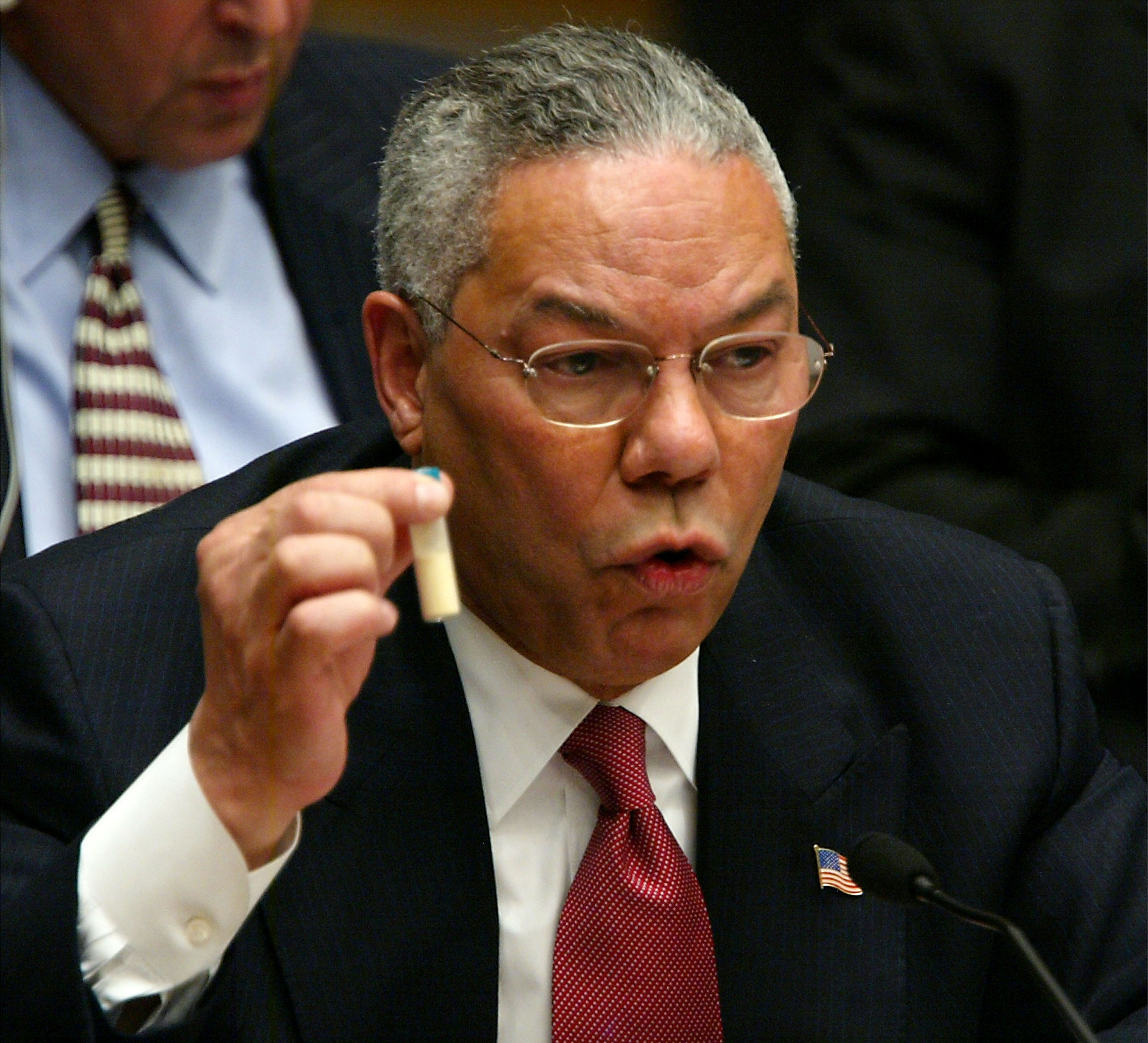 Sec. of State Powell holds a viral of anthrax while telling the UN that Iraq is hiding WMD. Feb 5, 2003.