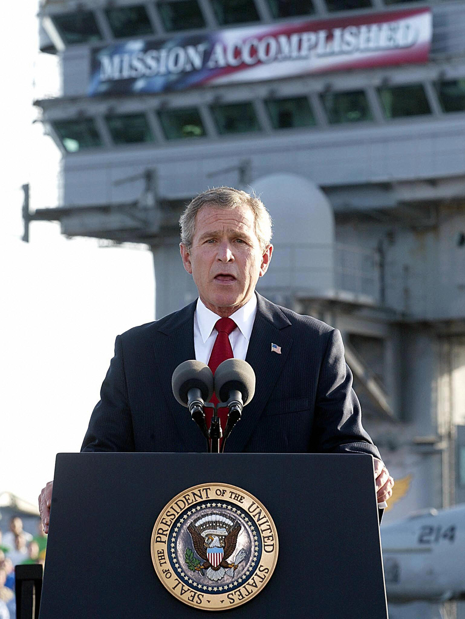 """Bush speaks beneath a banner reading """"Mission Accomplished"""" on the USS Abraham Lincoln, May 1, 2003."""