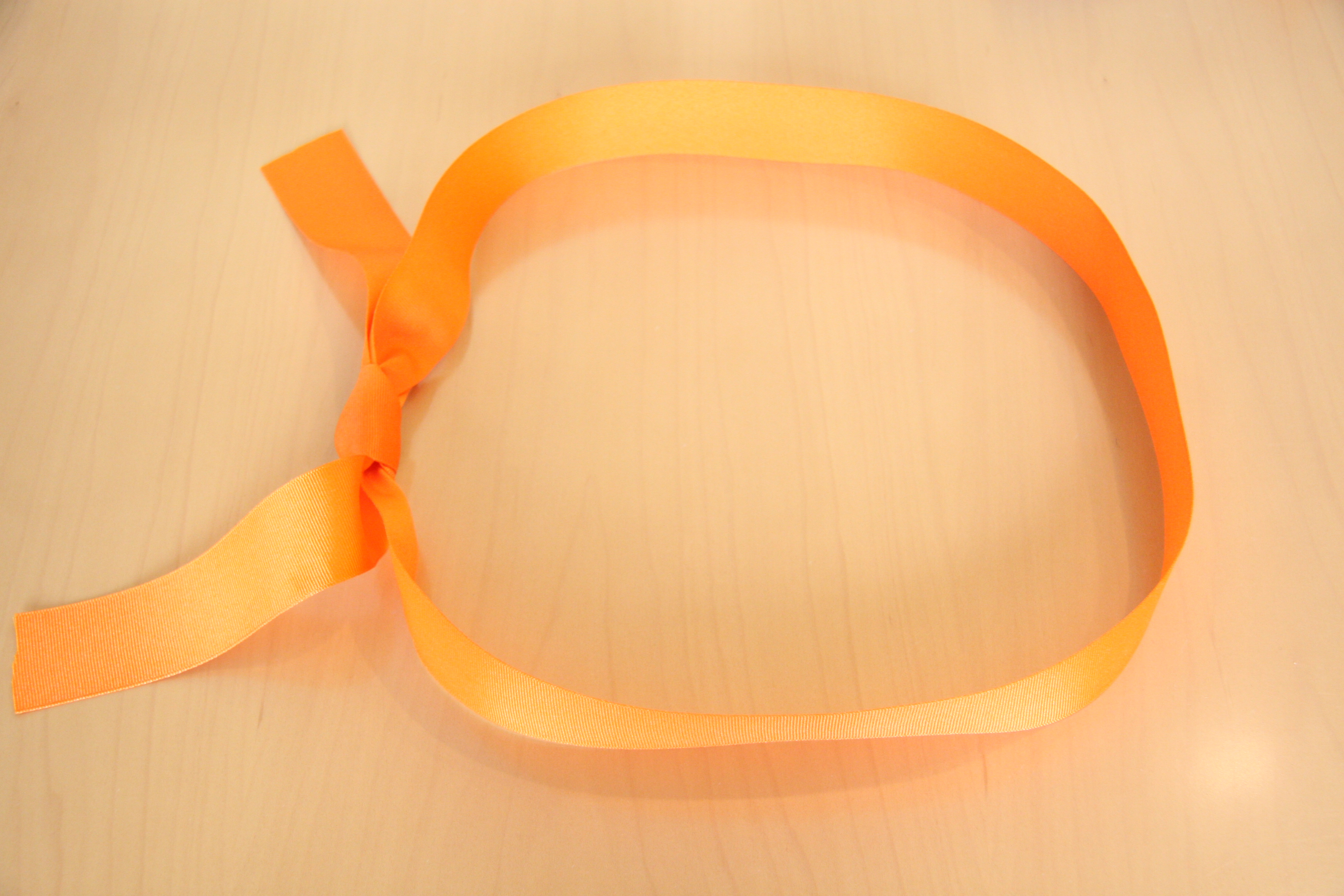 First, make a loop with the ribbon and tie a knot.