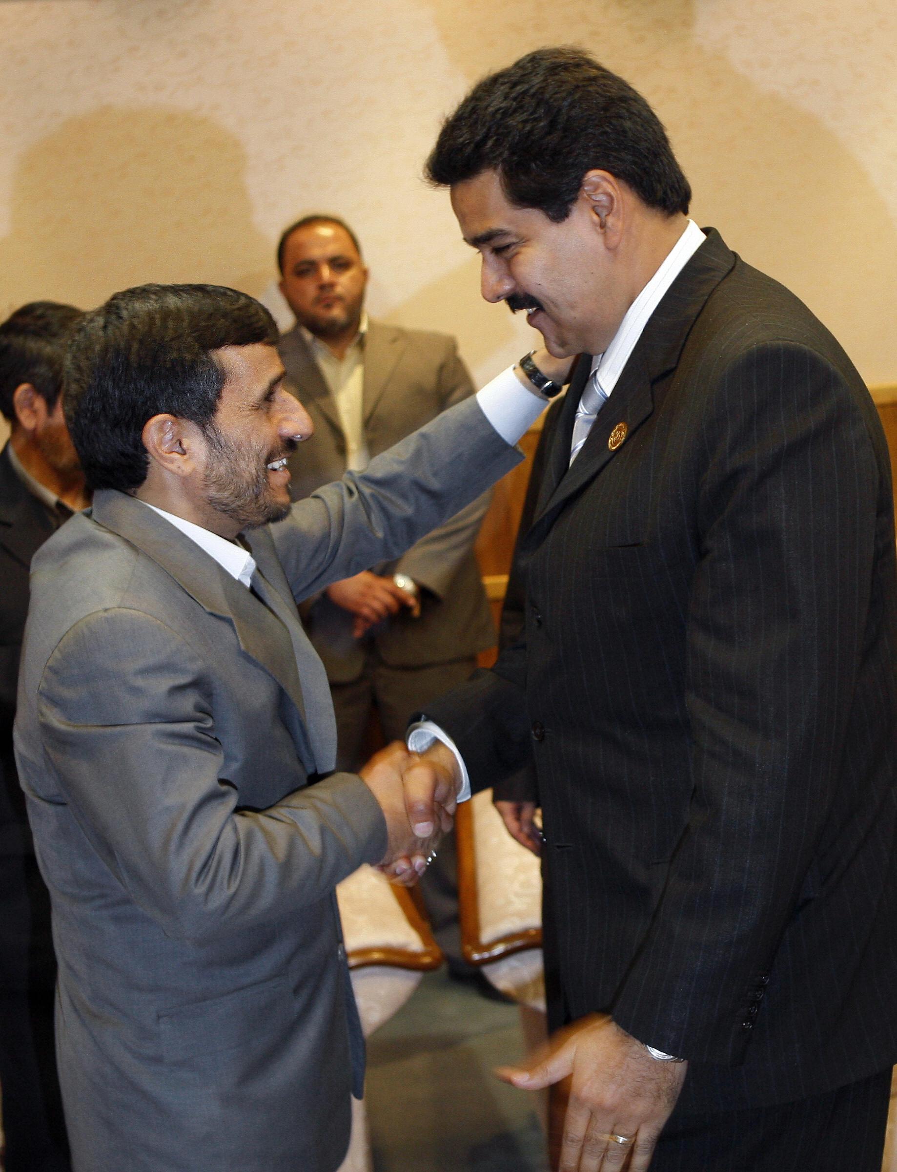 Iranian President Mahmoud Ahmadinejad  shakes hands with Venezuela's Foreign Minister Nicolas Maduro.