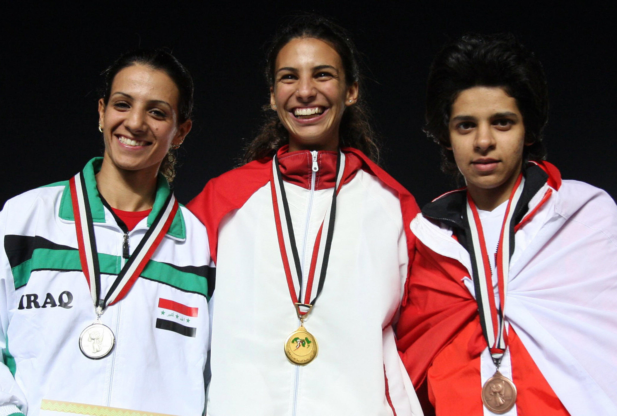 Dana Abdul Razzaq of Iraq (L) poses on the podium after winning the silver medal for the 100m race during the Pan Arab Games.